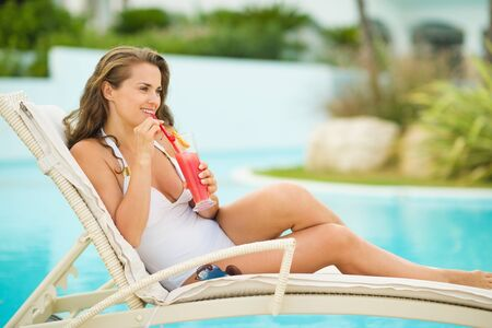 Happy young woman laying on sunbed and drinking cocktail Stock Photo - 17934017