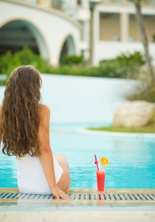 Young woman sitting at poolside with cocktail. rear view Stock Photo - 17933976