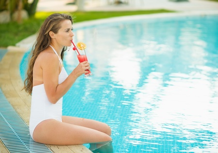 Happy young woman sitting at pool and drinking cocktail Stock Photo - 17934004