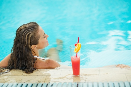 Young woman at pool with cocktail. rear view Stock Photo - 17934019