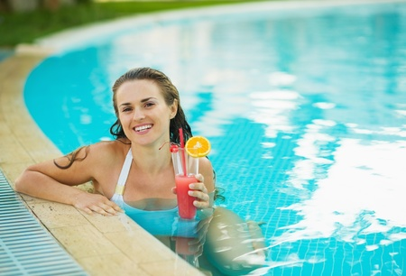 Portrait of smiling young woman at pool with cocktail Stock Photo - 17934005