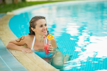 Happy young woman at pool with cocktail looking on copy space Stock Photo - 17934020