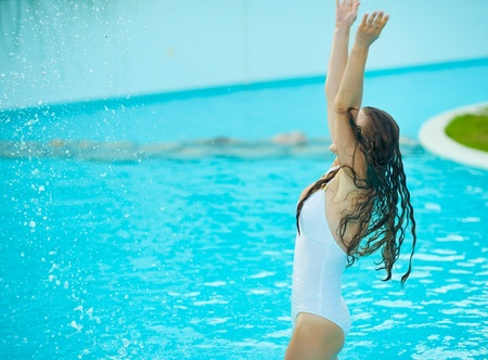 Happy young woman splashing water in pool Stock Photo - 17934029