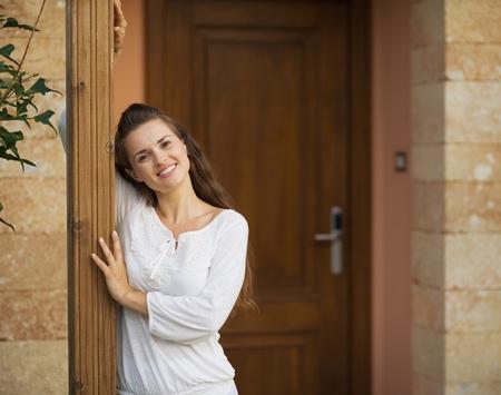 doorstep: Portrait of happy young woman at doorstep Stock Photo
