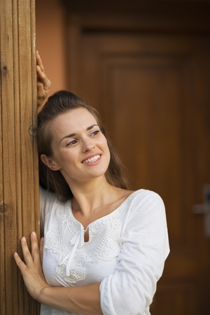 Happy young woman at doorstep looking on copy space Stock Photo - 17934026