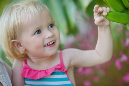 Curious baby exploring banana palm Stock Photo - 17934023