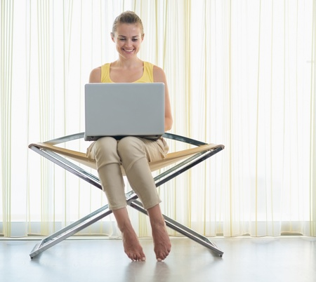 topicality: Smiling young woman sitting on modern chair with laptop Stock Photo