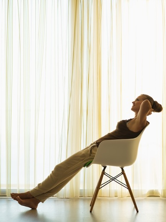 Silhouette of young woman relaxing in modern chair Stock Photo