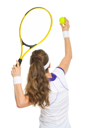 Tennis player ready to serve ball. rear view photo