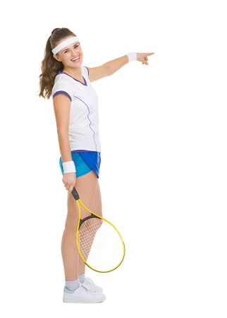 Full length portrait of happy tennis player pointing on copy space photo