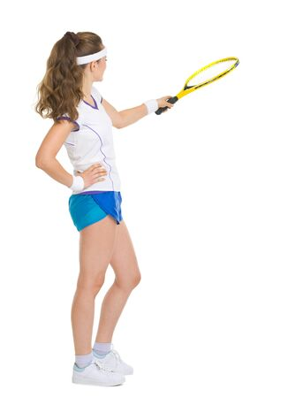 Full length portrait of happy tennis player pointing with racket on copy space photo