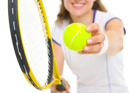 Closeup on racket and ball in hand of tennis player ready to serve photo