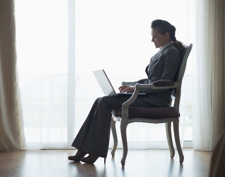 topicality: Silhouette of business woman working on laptop