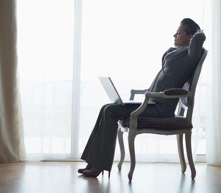 topicality: Silhouette of relaxed business woman sitting with laptop Stock Photo