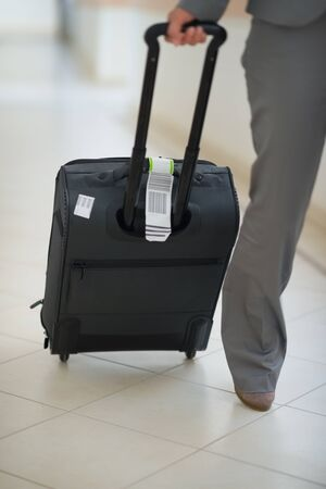 Closeup on business woman with bag on wheels photo