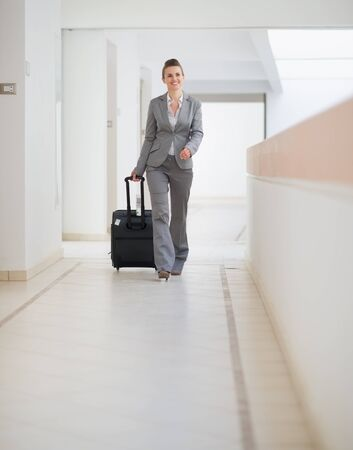 Business woman walking with bag on wheels photo