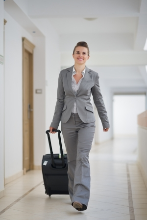 Happy business woman walking with bag on wheels photo