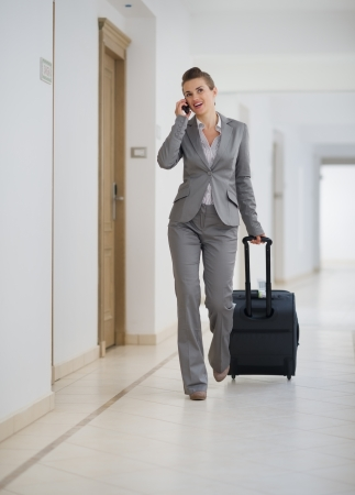 Business woman walking with bag on wheels and talking mobile phone photo