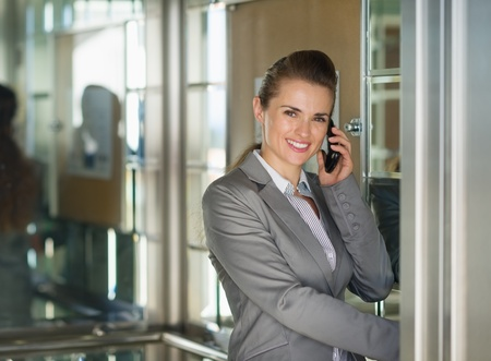Smiling business woman talking cell phone in elevator photo