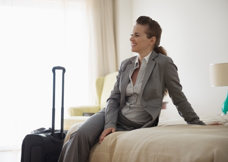 business traveller: Smiling business woman sitting on bed in hotel room Stock Photo