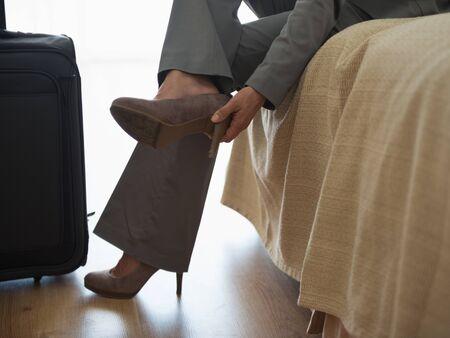 weariness: Mujer de negocios cansada de tomar los zapatos en la habitaci�n del hotel despu�s del viaje Foto de archivo