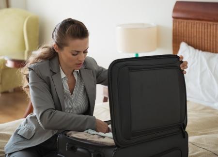 uitpakken: Business vrouw uitpakken bagage in hotelkamer