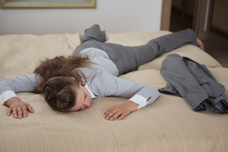 exhaustion: Tired business woman fall down from exhaustion in hotel room Stock Photo