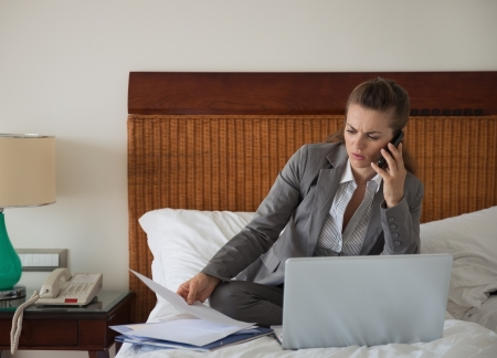 Business woman working with documents on bed in hotel room photo