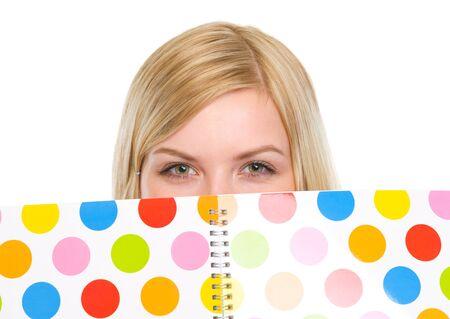 classbook: Closeup on student girl hiding behind notebook Stock Photo