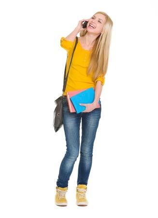 blabber: Full length portrait of smiling student girl talking mobile phone