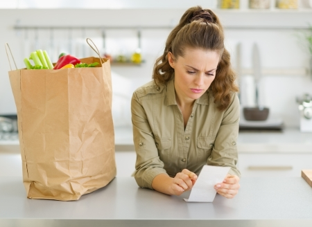 Concerned housewife checking bill after shopping in kitchen photo