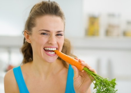 Happy young woman eating carrot in kitchen photo