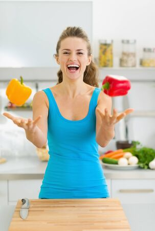 good mood: Happy young woman juggling with bell peppers in kitchen Stock Photo