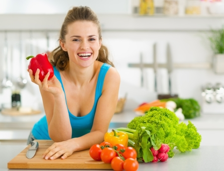 Portrait of happy young woman ready to make vegetable salad Stock Photo - 18347541