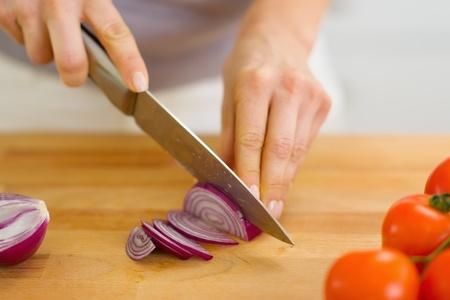 Closeup on woman cutting red onion photo