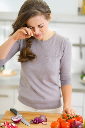 Young housewife crying while cutting onion photo