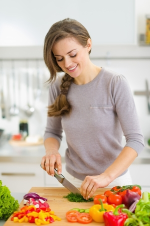 Happy young housewife cutting fresh dill in kitchen photo