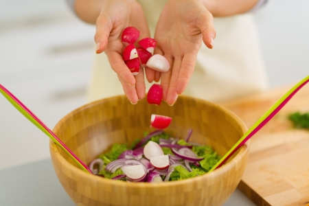 Closeup on housewife adding radishes into vegetable salad photo