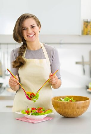 Happy young housewife served plate with fresh vegetable salad in kitchen photo