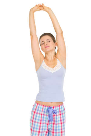 Young woman in pajamas stretching after sleep photo