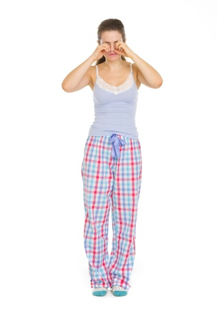somnolence: Young woman in pajamas rubbing eyes