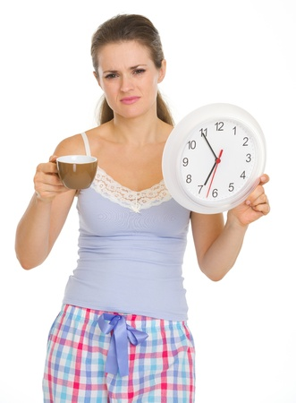 Frustrated young woman in pajamas with cup and clock Stock Photo - 18493240