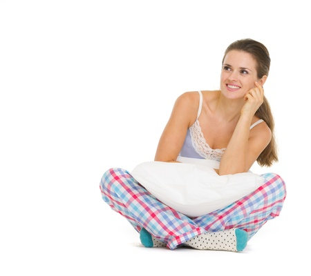 Happy young woman in pajamas sitting with pillow Stock Photo - 18493313