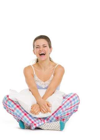 Smiling young woman in pajamas sitting with pillow Stock Photo - 18493318