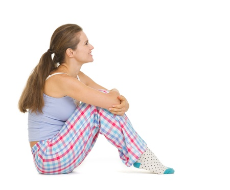 Happy young woman in pajamas sitting and looking on copy space Stock Photo - 18493316