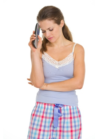 Frustrated young woman in pajamas with tv remote control photo