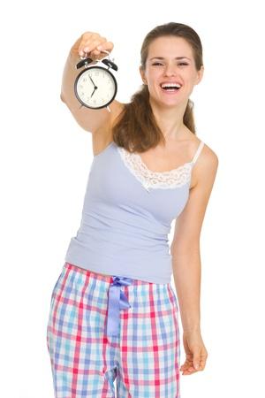 wakening: Happy young woman in pajamas showing alarm clock
