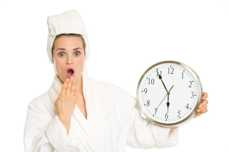 tardiness: Surprised young woman in bathrobe with clock