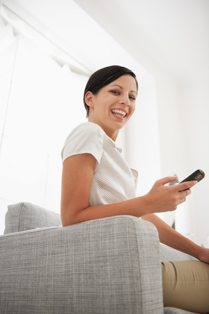 Happy young woman sitting on sofa with mobile phone Stock Photo - 18493217