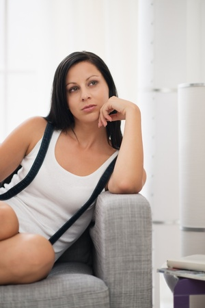 Thoughtful girl sitting on sofa in living room Stock Photo - 18493223